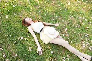 Asian woman lying on the grass.