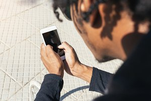 Afro young man using mobile phone.