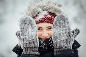 Female peeking through snowy gloves