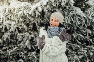 Happy woman feeling cold in winter