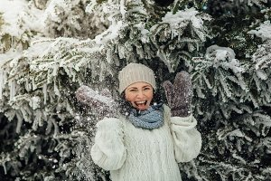 Happy woman having fun with snow