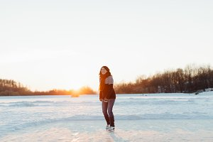Female skater ice skating on a lake