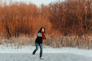 Woman ice skating on a frozen pond