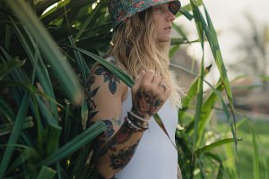 Portrait of beautiful young tattooed smiling woman standing in green leafy bush