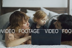 Young family with cute little girl playing with daughter while she watching laptop computer lying in bed at home