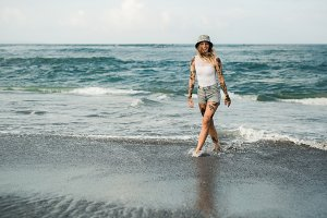 Tattooed woman walking at beach