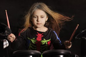 Little caucasian girl drummer with multicolored hair playing the electronic drum kit