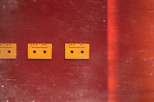Retro audio tape tapes lie on a red background, isometric projection, flat design