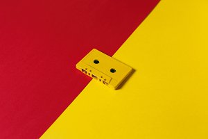 Retro audio tape tapes lie on a red and yellow background, isometric projection, flat design