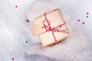 Women is holding a small gift box in hands worn in white knitted mittens
