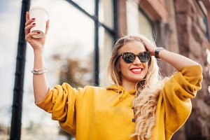 Stylish happy young woman wearing boyfrend jeans, white sneakers bright yellow sweetshot.She holds coffee to go. portrait of smiling girl in sunglasses