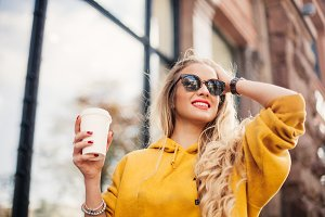 The concept of street fashion. young stylish girl student wearing boyfrend jeans, white sneakers bright yellow sweatshirt.She holds coffee to go. portrait of smiling girl in sunglasses