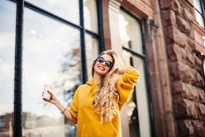 Pretty girl wearing sunglasses and bracelets smiling on the street. Outdoor portrait of laughing blonde young woman in mustard sweetshot standing near store.