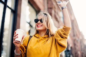 Stylish happy young woman wearing boyfrend jeans, white sneakers bright yellow sweatshirt.She holds coffee to go. portrait of smiling girl in sunglasses she greets friends