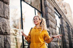 The concept of street fashion. young stylish girl student wearing boyfrend jeans, white sneakers bright yellow sweetshot.She holds coffee to go and dance . portrait of smiling girl in glasses
