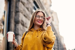Good-looking blond girl with long hair while walking down the street Outdoor portrait of fair-haired young woman in bright sweatshirt and trendy bracelets.smiling girl in glasses