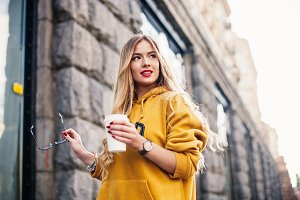 Pensive blond woman posing on modern streets, drinking coffee or cappuccino Street fashion concept, young woman wearing boyfrend jeans,glasses, white sneakers bright yellow sweetshot