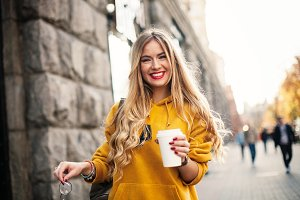 The concept of street fashion. young stylish girl student wearing boyfrend jeans, white sneakers bright yellow sweetshot.She holds coffee to go. portrait of smiling girl in sunglasses and with bag posing in the street