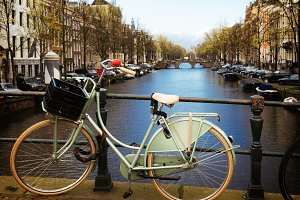 Old bicycle next to canal of Amsterdam