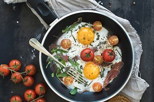 Pan of fried eggs, bacon and cherry-tomatoes