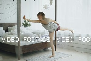 Happy attractive woman doing yoga exercise near bed in bedroom at home