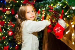 Cute toddler girl checking her Christmas stocking under a beauti