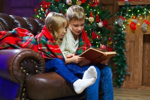 Children reading an interest book sitting on the bed against the