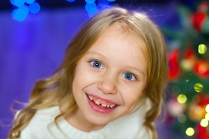 A large portrait of a child on a background of Christmas lights