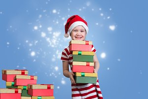 Happy child with a mountain of gifts. Emotional portrait. Delight girl in Christmas hat