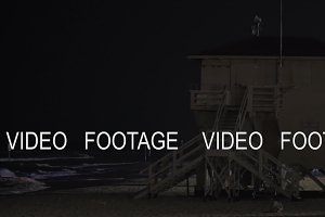 Lifeguard tower with blinking light on the beach at night