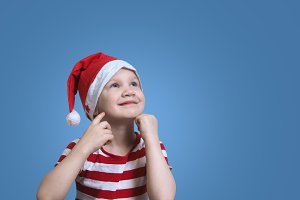 Little girl in Christmas hat dreams. Emotive portrait of happy child