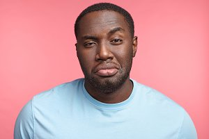 Plump dark skinned African guy raises eyebrow, has full lips, tired and sleepless expression, isolated over pink background. Black man poses in studio. People, lifestyle, expressions concept