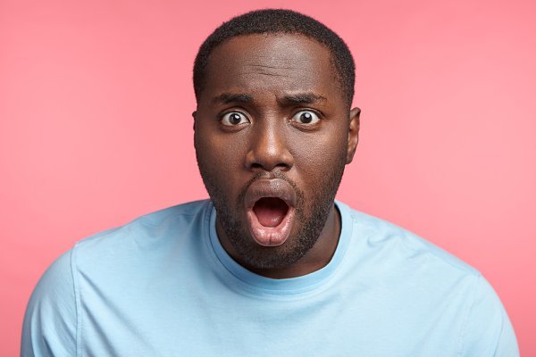 Shocked black man stares at camera, opens mouth widely, can`t ...