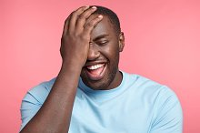 Positive human expressions concept. Dark skinned male laughs at good joke, keeps hand on head, expresses natural feelings, understands anecdote later than others, has slow reaction, carefree smile