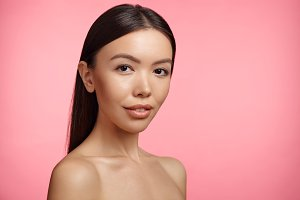 Beautiful young woman with Asian appearance, poses naked, has healthy clear skin, stands over pink background. Head and shoulders of extraordinary female. Skin care concept. Perfect naked body