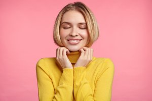 Contented female closes eyes with enjoyment, being glad to buy very convinient warm yellow turtleneck sweater, feels pleased, has rest at home. Young woman advertises high quality cotton clothes