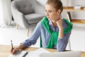 Portrait of thoughtful woman wears casual clothes, sits at table, writes in diary, makes notes, being at home. Busy female in spectacles looks pensively aside, works on developing new strategy