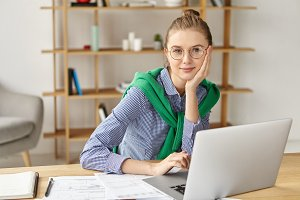 Beautiful confident young female writer uses laptop computer for work, looks directly into camera with pleased expression. Busy student has appealing appearance, works on diploma paper in Maths