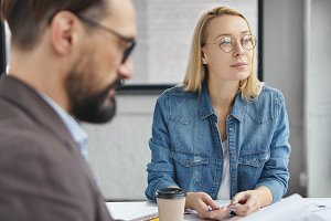 Thoughtful beautiful blonde woman in round spectacles and denim shirt sits with his boss, work together at startup project, surrounded with sheet of papers and cup of coffee. Collaborative work.