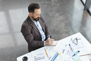 Top view of handsome skilled professional employer dressed formally, sits at work place, surrounded with many documents, writes with pencil in papers. Male marketing specialist works indoors