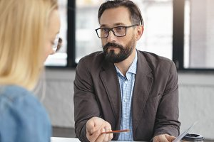 Serious bearded mature man with beard, dressed formally interviews female job applicant, asks tricky questions, checks her knowledge and abilities. Two coworkers discuss working schedule together