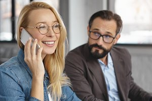 Cheerful blonde attractive woman makes business phone, sits next to colleague who listens to conversation attentively, tries to hear everything, has curious expression. Partners gather together
