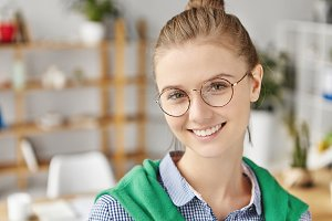 Close up portrait of glad smiling female wears round glasses and casual shirt, stands over office interior, has good mood after finishing working day. Attractive woman has appealing appearance