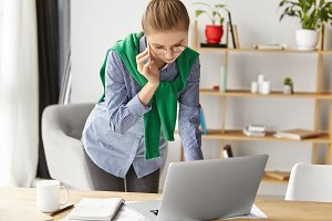 Busy young female office worker stands at work desk, searches information on generic laptop computer, uses smart phone for communication, gives consultation, manages finances and figures indoors