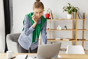 Portrait of female freelancer works remotely at home, uses smart phone for connecting with boss and modern laptop computer, stands at working place near table with papers and cup of hot coffee