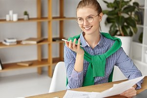 Happy delightful female financier expert wears shirt and green sweater on shoulders, works with documents, makes voice call to boyfriend, glad to hear compliments and support. Job and work concept