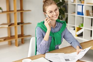 People, business conversation concept. Cheerful young female manager has conversation over smart phone, arranges meeting, holds documents and papers, sits at work place, studies necessary information