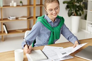 Smiling businesswoman dressed casually, looks at business report, writes down information in spiral notebook, analyzes graphics, has happy expression as almost finishing work, going have dinner break