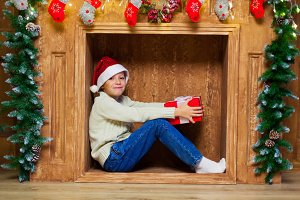 christmas child in a fireplace with a red gift box