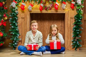 Portrait of happy children with presents around the Christmas tr